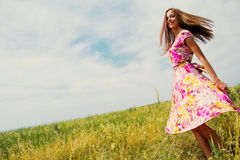 Happiness. Candid skipping carefree adorable woman in field of flowers at summer sunset Stock Image