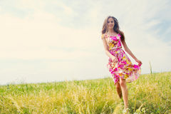 Happiness. Candid skipping carefree adorable woman in field of flowers at summer sunset Stock Photography