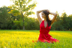 Happiness. Candid skipping carefree adorable woman in field of flowers at summer sunset Royalty Free Stock Images