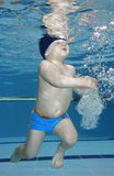 Happiness. Underwater picture of a baby boy swimming and playing Stock Photos