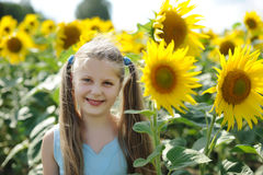 Happiness. An image of a happy little girl and sunflowers royalty free stock photos