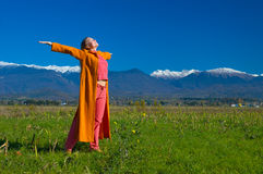 Happiness. Young, attractive, fit, woman enjoing autumn sun. Green grass blue sky and mountains with snow Stock Images