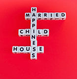 Happiness. Text ' happiness, married, child, house ' inscribed in black uppercase letters on small white cubes arranged crossword style, red background Royalty Free Stock Photos