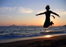 Happiness. Girl jumping at sunset Stock Image