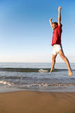 Happiness. Young man takes a great leap on a beach at sunrise: happiness, fitness, success concept Royalty Free Stock Images