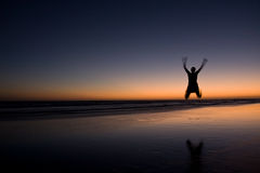 Happiness. Girl is jumping for joy on the beach during sunset royalty free stock photos