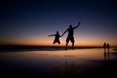 Happiness. Young happy couple is jumping for joy on the beach during sunset royalty free stock photo