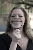 Happiness. A wide wide smile through a magnifying glass Royalty Free Stock Photo