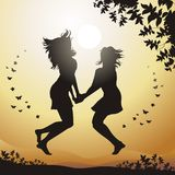 Happiness. Two girls jump with happiness against a sunset Stock Photo