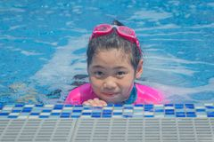 Happiness Asian cute little girl has feeling funny and enjoy in swimming pool. stock photos