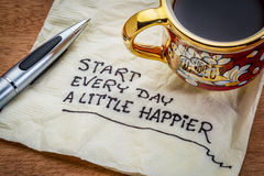 Happiness and attitude concept on napkin. Start every day a little happier - happiness and attitude concept - handwriting on a napkin with cup of coffee Stock Photo