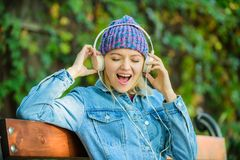 Happiness. audio book. style and music. hipster woman in headphones. modern technology instead of reading. relax in park royalty free stock images