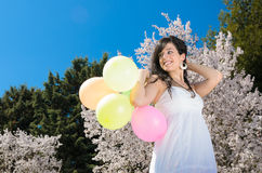 Happiness with Balloons. Young beautiful woman playing with colorful balloons, smiling and celebrating love and life in a spring scene Royalty Free Stock Photography