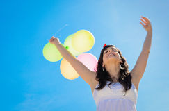 Happiness with Balloons. Beautiful brunette woman shows her happiness playing and having fun with colorful balloons and blue sky background Royalty Free Stock Photography