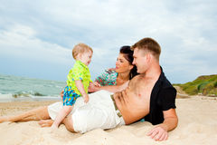 Happiness at the beach. Happy kid talking to his parents at the beach Stock Image