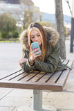 Happiness beautiful girl with smart phone lying on the bench. Stock Photography