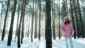 Happiness, beautiful, happy girl runs between trees in woods, winter fun, flirting young woman looking into camera. Winter forest, sun`s rays shine through stock video