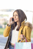 Happiness beautiful latin woman with shopping bags talking by ph. Smiling woman with shopping bags talking by phone Royalty Free Stock Image