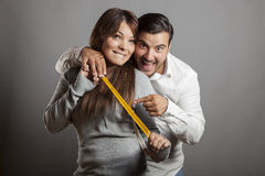 Happiness and boldness couple showing off sex length. The boldness couple shows the sex length with a tape measure Royalty Free Stock Photos