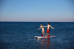 Happiness boy and girl holding hands on sup surf swimming at the ocean. Concept lifestyle, sport, love Royalty Free Stock Photo