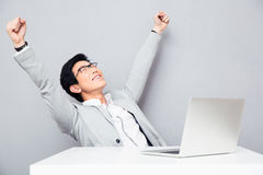 Happiness businessman sitting at the table with laptop Royalty Free Stock Images