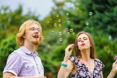 Couple blowing soap bubbles, having fun stock images