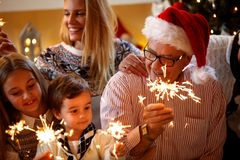 happiness, Christmas, family concept-family with sprinklers Christmas holidays. royalty free stock photos