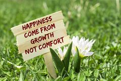 Happiness come from growth not comfort. On wooden sign in garden with spring flower Stock Image