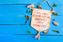 Happiness come from growth not comfort text on Paper Scroll. With dried flower around and blue wooden background royalty free stock photography