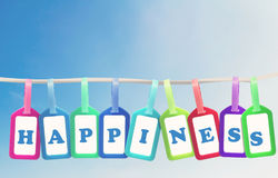 Happiness Concept Background. Happiness concept, group of plastic tag and text on blue sky background stock image