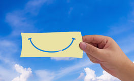 Happiness Concept Background. Happiness concept, hand and paper smile on blue sky background royalty free stock photography