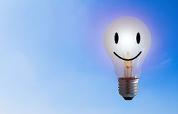Happiness Concept Background. Happiness concept, light bulb smile on blue sky background royalty free stock photos