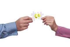 Happiness concept. Close up of hands holding puzzle pieces of smiley as happiness concept Stock Photo