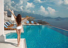 Happiness concept. Luxury travel vacation Free Woman sunbathing. By infinity swimming pool at luxurious resort Royalty Free Stock Photo