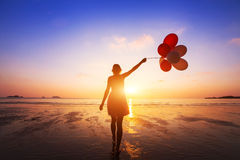 Happiness concept, positive emotions, happy girl. With multicolored balloons enjoying summer beach at sunset Stock Photography