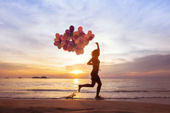 Happiness concept, psychology of happy people. Young woman running with multicolored balloons on the beach Royalty Free Stock Image