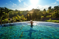 Happiness concept. Woman sunbathing in infinity swimming pool at royalty free stock photo