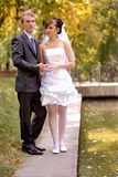 Happiness couple. The bride and groom, standing near the lake in the park on a beautiful sunny day royalty free stock image