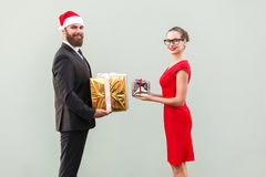 Happiness couple looking at camera with toothy smiling and give. Each other gift box, in honor of christmas. Studio shot. Isolated on gray background Stock Photo