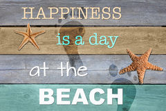 Happiness is a day at the beach. Beach themed colors, starfish, footprints on the wood and the phrase `Happiness is a day at the beach stock illustration