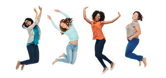Happy women jumping in air over white background. Happiness, diverse, motion and people concept - happy international women jumping in air over white background Royalty Free Stock Images