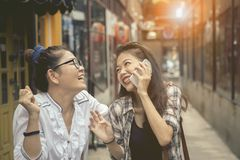 Happiness emotion of asian two asian woman talking to smart phon. Happiness emotion of asian two asian women talking to smart phone and laughing in shopping Stock Photo