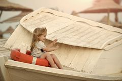 Happiness and expressive emotions. Childhood and baby care concept. Small kid sit on wooden boat at beach. Marine safety and transport. Boy little child stock photo