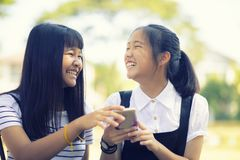 Happiness face of asian teenager holding smart phone in hand with toothy smiling face stock photos
