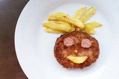 Happiness face of fried burger with fries on the plate. Royalty Free Stock Photos