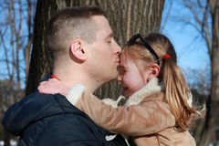 Happiness. Father kissing his daughter outdoors Royalty Free Stock Image