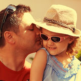 Happiness. Father kissing his daughter outdoors. Summer background. Closeup portrait Royalty Free Stock Photography