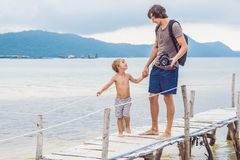 Happiness father and son on the pier at sunny day under sunlight royalty free stock images
