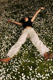 Happiness in the flowers. Happy girl rolling in the flowers Royalty Free Stock Photography