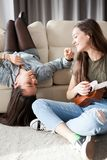 Happiness and friendship. Two girls in the bedroom having fun. And one is playing at a small guitar stock photo